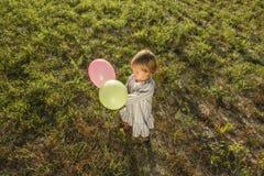 Het mooie meisje spelen met ballons op het gebied royalty-vrije stock afbeeldingen