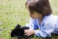 Het mooie meisje spelen met een konijn Stock Afbeeldingen