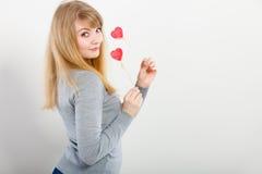 Het mooie meisje spelen met harten op stokken Stock Fotografie