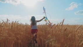 Het mooie meisje spelen met vlieger op tarwegebied op de zomerdag Kinderjaren, levensstijlconcept stock video