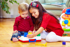 Het mooie meisje spelen met weinig broer thuis Royalty-vrije Stock Foto