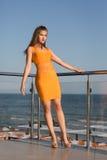 Het mooie meisje stellen op een balkon op een blauwe hemelachtergrond Een sexy dame in een korte oranje kleding met lang donker b royalty-vrije stock afbeelding