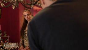 Het mooie meisje stellen voor een fotograaf in retro stijl de manierindustrie, schoonheid, coulisse stock footage