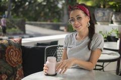 Het mooie meisje stelt in bestratingskoffie, glimlacht, houdt de melkcocktail in handen, royalty-vrije stock foto's