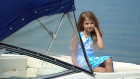Het mooie meisje stelt voor foto's op de boot op water bij een pijler Een beetje het blonde meisje zit op de boot stock footage