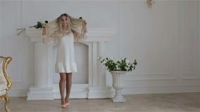 Het mooie meisje toont haar lang wit en haar die wervelen dansen stock videobeelden