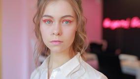 Het mooie meisje toont haar vreemde heldere de lentemake-up aan stock videobeelden