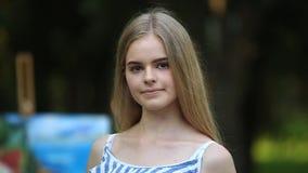 Het mooie meisje trekt een beeld in het park stock videobeelden