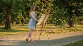 Het mooie meisje trekt een beeld in het park gebruikend een palet stock videobeelden