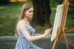 Het mooie meisje trekt een beeld in het park gebruikend een palet met verven en een spatel Royalty-vrije Stock Afbeeldingen