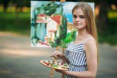 Het mooie meisje trekt een beeld in het park gebruikend een palet met verven en een spatel Stock Foto's