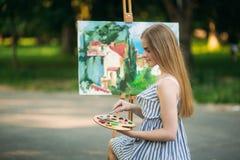 Het mooie meisje trekt een beeld in het park gebruikend een palet met verven en een spatel Royalty-vrije Stock Fotografie