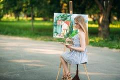 Het mooie meisje trekt een beeld in het park gebruikend een palet met verven en een spatel Stock Afbeelding