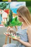 Het mooie meisje trekt een beeld in het park gebruikend een palet met verven en een spatel Stock Fotografie