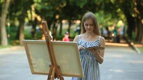 Het mooie meisje trekt een beeld in het park gebruikend een palet met verven en een spatel Schildersezel en canvas met een beeld  stock video