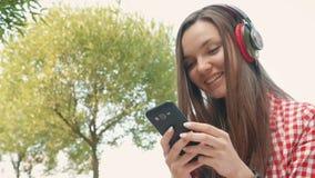 Het mooie meisje typt een bericht op smartphone stock video