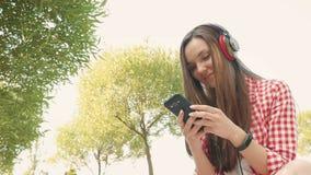 Het mooie meisje typt een bericht op smartphone stock footage