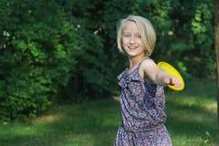 Het mooie het meisje van het blondejonge geitje spelen met frisbee in park Actief sportenspel in openlucht Stock Afbeelding