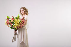 Het mooie meisje van de blondelente met grote boeketbloemen Stock Foto