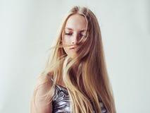 Het mooie meisje van de blondevrouw met lang blond vlot haar en galant stock fotografie