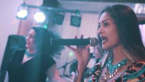 Het mooie meisje van de meisjeszigeuner zingt bij de club op de microfoon Vocalistclose-up Zigeunerlied Art stock videobeelden