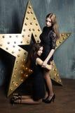 Het mooie meisje van meisjes knielende omhelzingen Stock Fotografie