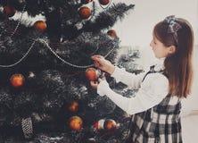 Het mooie meisje verfraait grote Kerstmisboom Stock Foto