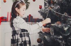 Het mooie meisje verfraait grote Kerstmisboom Royalty-vrije Stock Foto