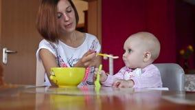 Het mooie meisje voedt haar baby stock footage