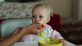 Het mooie meisje voedt haar baby stock videobeelden