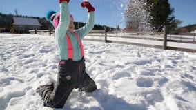 Het mooie Meisje in Warme Kleding werpt Sneeuw het Spelen buiten tijdens Warm Sunny Day Wintertijd en Kinderjarenconcept stock videobeelden
