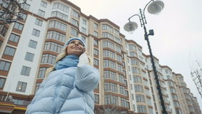 Het mooie meisje in warme kleren spreekt in openlucht op de telefoon stock video