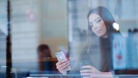 Het mooie meisje warmt met een hete koffie in een comfortabele café op, zit door het venster en gebruikt haar telefoon Moderne L stock footage