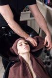 Het mooie meisje wast haar haar vóór een kapsel in een schoonheidssalon haarwas bij het kappen, jong Kaukasisch meisje stock afbeeldingen