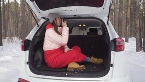 Het mooie meisje in witte auto op de winterdag in naald bos drinkt thee stock footage