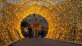 Het mooie meisje in witte borrels gaat door een kluis van gouden lichten stock videobeelden