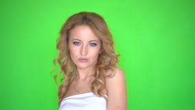 Het mooie meisje in witte kleding met krullend kapsel danst op groene het schermachtergrond stock footage