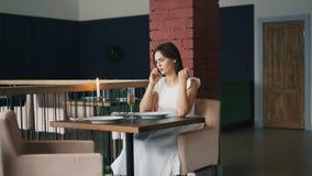 Het mooie meisje in witte kleding wacht op haar vriend in restaurant die dan hem roepen die aan hem spreken boos en stock video