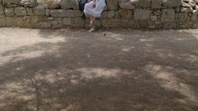 Het mooie meisje in witte sarafan zit op het metselwerk van een geruïneerd kasteel stock footage