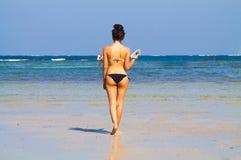Het mooie meisje wolking in het strand met een boek royalty-vrije stock afbeelding