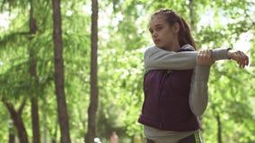 Het mooie meisje wordt klaar voor opleiding Jonge sportvrouw die in openlucht het uitrekken doen zich stock footage