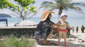 Het mooie meisje wrijft baby met zonnescherm stock footage