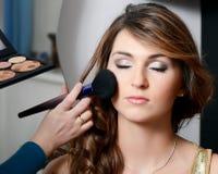 Het meisje zette de make-up op het gezicht Stock Foto's
