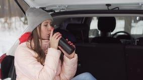 Het mooie meisje zit in auto op zonnige de winterdag, drinkt thee van een kleine thermosfles stock video