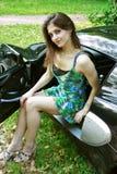 Het mooie meisje zit in de auto Stock Afbeelding