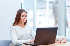 Het mooie meisje zit in een koffie en gebruikt laptop stock afbeelding