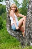Het mooie meisje zit op berk in een park Stock Afbeelding