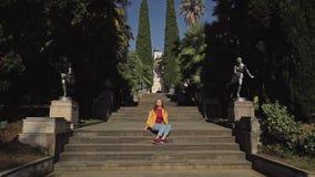 Het mooie meisje zit op de stappen van een reusachtige trap met standbeelden op een zonnige dag en geniet van de zon Er zijn weel stock videobeelden