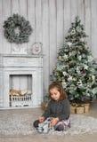 Het mooie meisje zit op een vloer en speelt thuis met houten stuk speelgoed dichtbij een open haard in Kerstmis royalty-vrije stock afbeelding