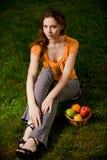 Het mooie meisje zit op groen gras Royalty-vrije Stock Afbeelding